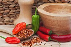 Crushed and whole chilli peppers in rustic kitchen setting Stock Photos