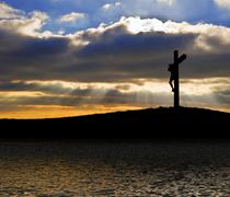 Jesus christ crucifixion on good friday silhouette reflected in lake water Stock Photos
