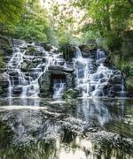 beautiful waterfall cascades over rocks in lush forest landscape - stock photo