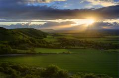 Stock Photo of stunning countryside landscape with sun lighting side of hills at sunset