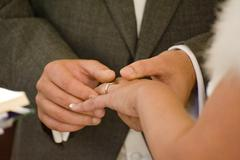Close up detail of groom putting wedding ring on bride's finger during real c Stock Photos