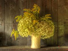 retro style still life of dried flowers in vase against worn wooden backgroun - stock photo