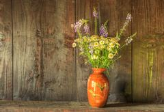 Retro style still life of dried flowers in vase against worn wooden backgroun Stock Photos