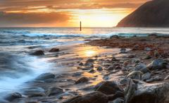 Beautiful vibrant sunrise over low tide beach landscape Stock Photos