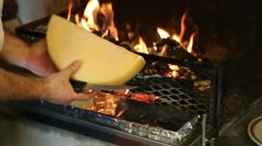 Raclette cheese warming up for serving in front of a fire - stock footage