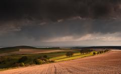 Stunning landscape with stormy sky over rural hills Stock Photos