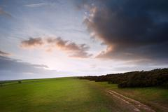 Countryside landscape path leading through fields towards dramatic beautiful Stock Photos