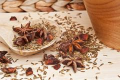 star anise and cumin seeds in rustic kitchen setting with wooden utensils - stock photo