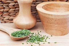 chopped chives in rustic kitchen setting with wooden pestle and mortar - stock photo