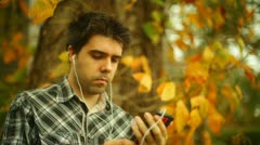 Listening music mp3 player fall Stock Footage