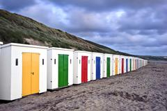 Row of colorful beach huts receding into distance on empty beach during drama Stock Photos