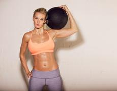 Sweaty athlete with ball on her shoulder Stock Photos