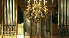 Church organ front behind chandelier - tilt up Stock Footage