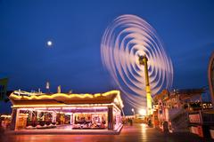 spinning vertical ride at carnival with moving light blur - stock photo