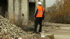Engineer talking on the  cell phone near the collapsed building Stock Footage