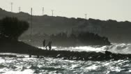 Stock Video Footage of people on a rock on a background of big waves