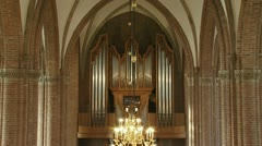 Church interior gothic arches, chandelier, organ front  Stock Footage