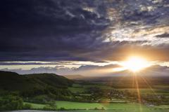 Stunning summer sunset over countryside escarpment landscape Stock Photos