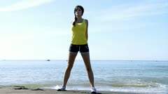 Beautiful female model doing gimnastic in front of the ocean Stock Footage