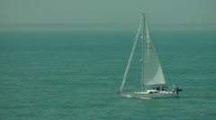 Yacht with white sail, sailing on calm blue sea, sailor in red jacket Stock Footage