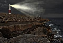 Victorian lighthouse on promontory of rocky cliffs with beam alight at night Stock Photos