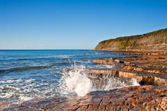 kimmeridge bay seascape with rock ledges extending out to sea on blue sky day - stock photo