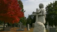 Statue of Girl with Arm Over Cross Faces the Graveyard Stock Footage