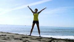 Beautiful gimnast training in front of the beach wide shot Stock Footage