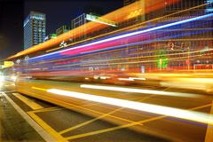 High speed and blurred bus light trails in downtown nightscape Stock Photos