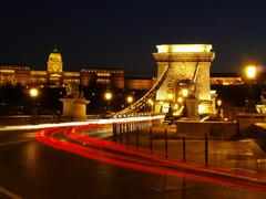 budapest chain bridge at night with cars. - stock photo