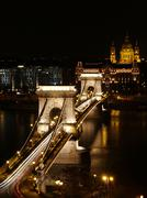 Chain bridge at night time with cars. Stock Photos