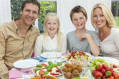 Parents children family healthy eating salad table Stock Photos