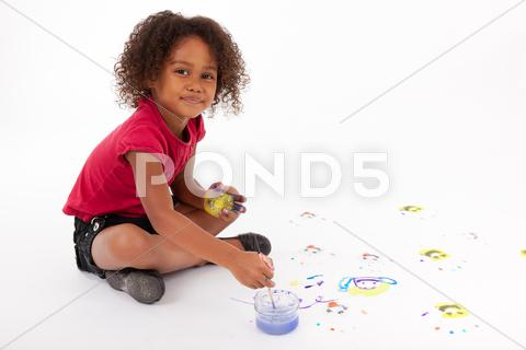Stock photo of little african asian girl painting on the floor