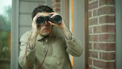 Paranoid scared binoculars voyeur look Stock Footage