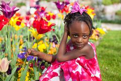 Cute little african american girl playing in the garden Stock Photos
