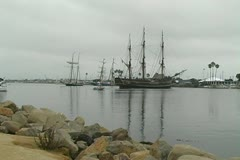 HMS Bounty and Tall Ship moving into channel away from dock Stock Footage