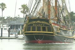 Stern of HMS Bounty backing up from dock into channel Stock Footage