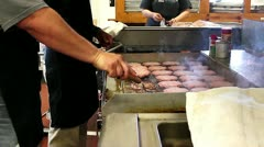 Flipping hamburgers on a professional grill Stock Footage