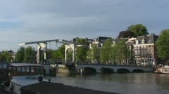 Draw bridge crossing river Amstel + cyclists Stock Footage