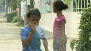 Stock Video Footage of Asian Boy Spraying The Hose During Songkhran Water Festival
