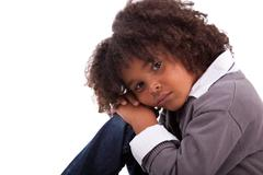 portrait of an african american little boy sitting on the floor - stock photo