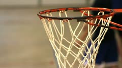 Boy shooting basketball in out of focus distance and ball goes in hoop. Stock Footage