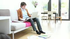 Male sitting on sofa in living room working on laptop Stock Footage