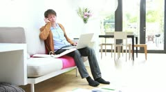 Male sitting on sofa in living room working on laptop and calling Stock Footage