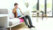 Stock Video Footage of Male sitting on sofa in living room working on laptop and calling