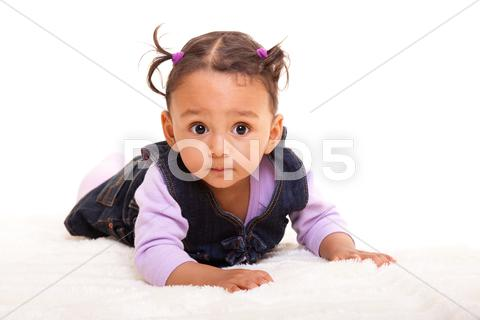 Stock photo of beautiful biracial baby girl lying on the floor