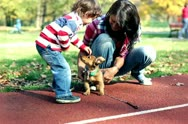 Stock Video Footage of Young mother playing with her son and puppy in autumn park, steadycam