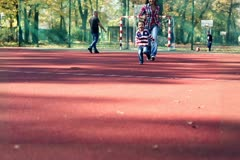 Young mother with her son running on playing field in autumn Stock Footage