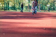 Stock Video Footage of Young mother with her son running on playing field in autumn