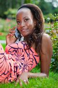 teenage black girl using a phone, lying on the grass - stock photo